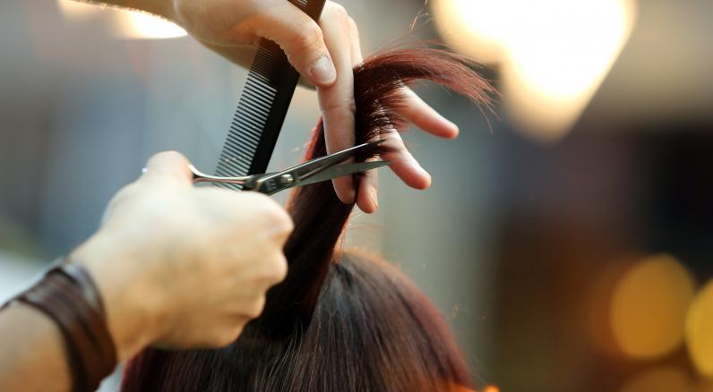 Curso de estilista GRATIS manos con una tijera cortando el pelo de una mujer