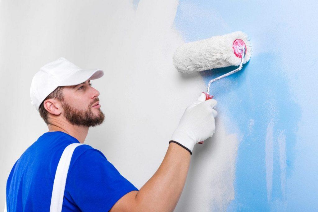 Pintor pintando de azul una pared con salida laboral