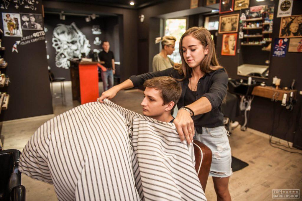 Mujer barbera cortando el pelo