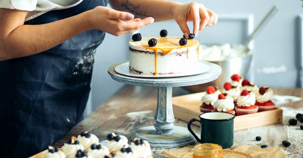 Mujer repostera decorando una torta dulce