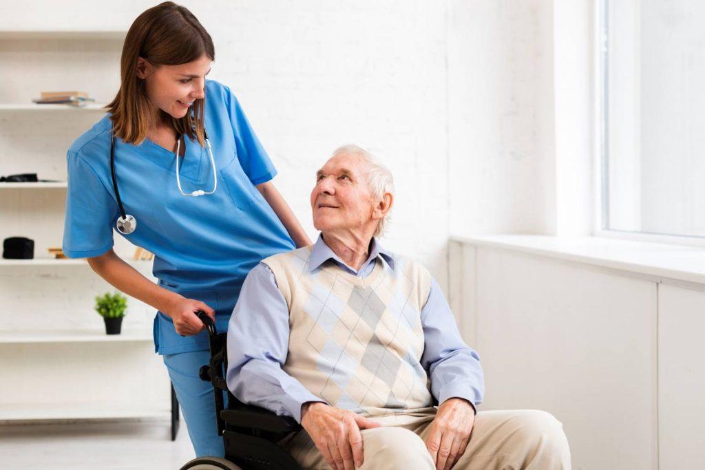 Enfermera cuidando anciano en silla de ruedas