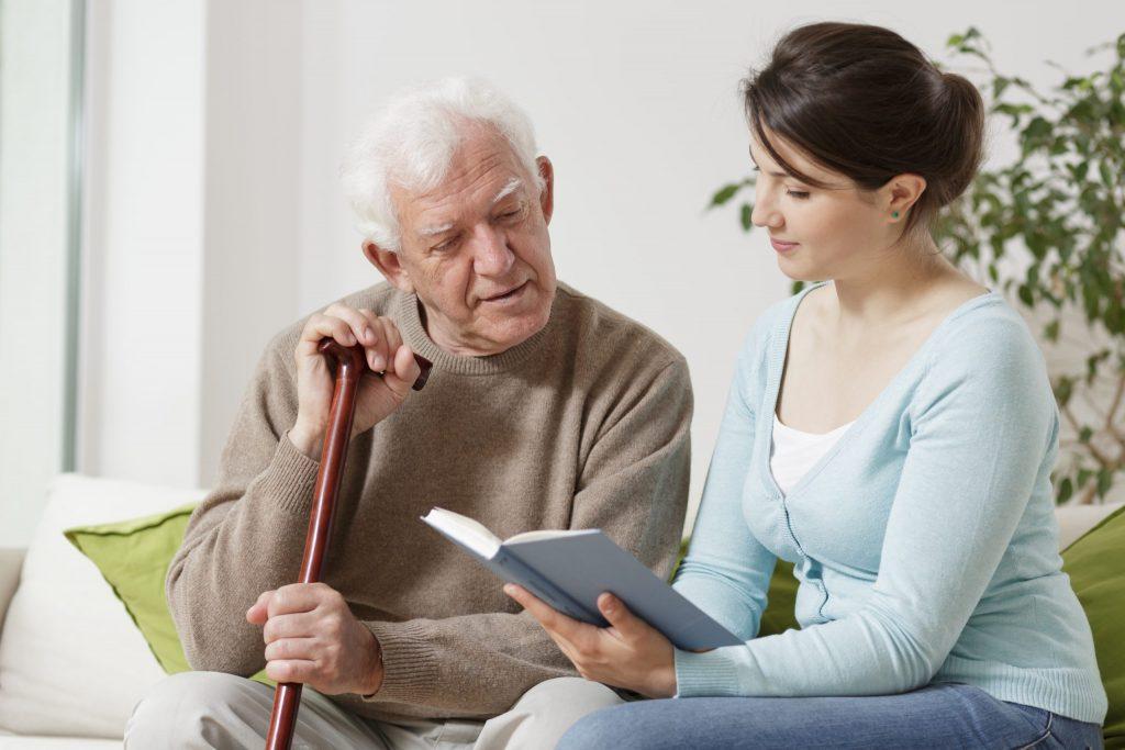 Cuidadora de adultos mayores leyéndole un libro a un adulto mayor
